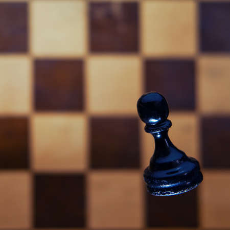 Chess black pawn against the background of a vintage chessboard from the Soviet Union. Tournament, game and study of chess, concept