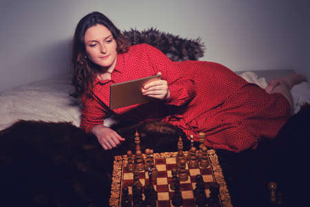Young woman plays chess with a computer program on a tablet. Playing chess at home online via the Internet