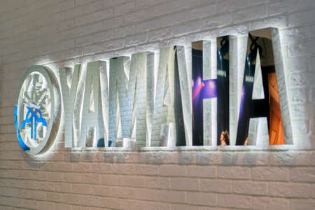 Yamaha brand inscription and logo on the wall of a musical instrument store Editorial