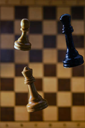 Flying in the air chess pieces on the background of the chessboard. Concept of problems of playing and learning chess