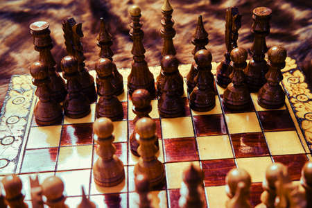 Vintage wooden chess set with queen gambit opening, close-up view of the chessboard.