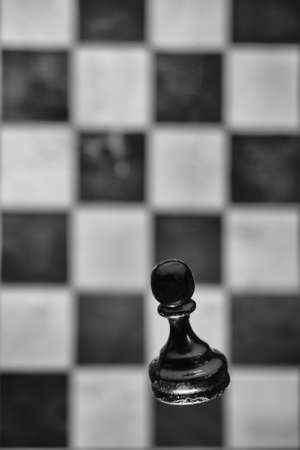Black chess pawn and old shabby monochrome chessboard. Tournament, game and study of chess, concept