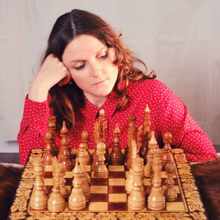 Young woman playing chess while sitting at the chessboard at home, closeup portrait