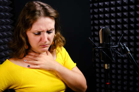 Young woman coughs next to the microphone and holds her throat. Trouble with the voice of the singer in the performance of the song. Difficulties with his health and vocal chords from a musician.