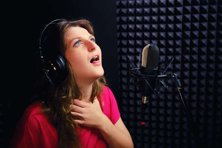 Loss of voice at the singer when recording a song. Fatigue vocalist, problems with the throat and vocal cords. Recording Studio, black background, professional microphone.