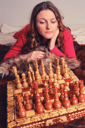 Portrait of a woman in a red dress with curly hair on the bed next to the chess set.