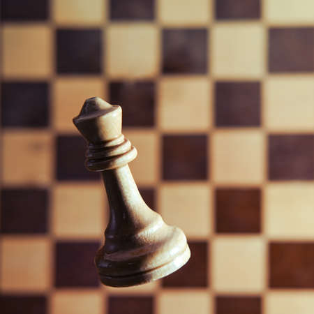 White chess piece queen on the background of the retro chessboard. Tournament, game and study of chess, concept