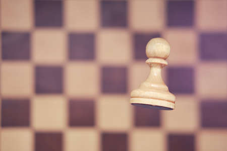 White chess piece pawn and vintage shabby chessboard. Competition and game study, concept