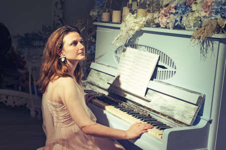 A young woman sits at a vintage piano. A pianist at a musical instrument decorated with candles and flowers Standard-Bild