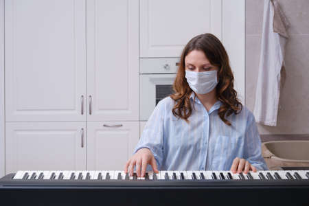 A musician at a digital piano wearing a medical face mask. A woman plays a home musical instrument during the pandemic Stock Photo