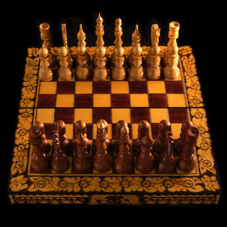 Carved chess pieces are placed opposite each other before the start of the game