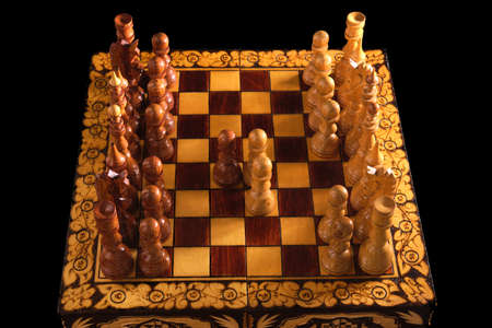 Chessboard with Queen Gambit opening on black background, carved chess