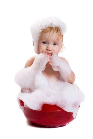 washbasin: Cute bating child in red wash-basin with big volume bubble bath on his head and body, isolated. See the whole series in my portfolio Stock Photo