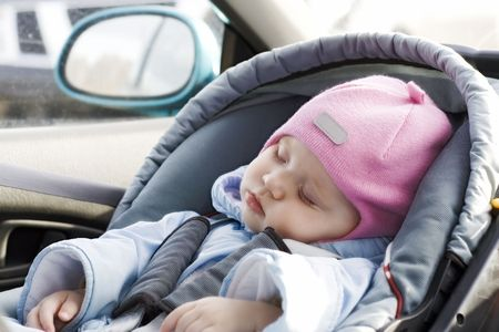 car side: Little baby sleeping in a car in a child`s car seat Stock Photo