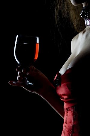 allurement: Pretty tempting and sexy decollete woman in red corsage with wineglass full of red drink (wine, juce)