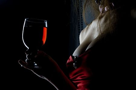 Pretty tempting and sexy decollete woman in red corsage with wineglass full of red drink (wine, juce)