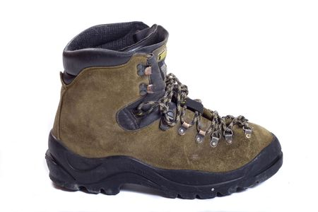 Leather boot, for climbing and hiking, well worn, little mud around the soles, sideview, isolated on white photo