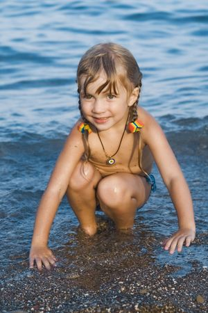 little girl bath: Pretty cheerful girl sitting on a sand  in the sea-water after swimming