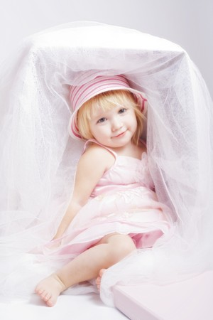 baby doll: Pretty baby-girl in beautiful pink dress and bonnet sit in big box like a doll