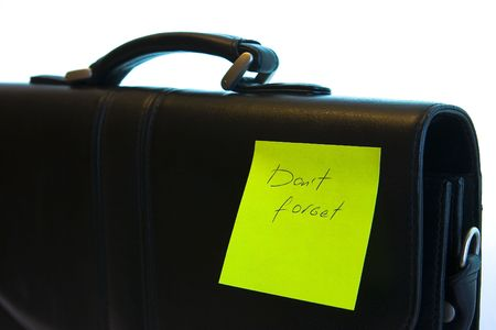 admonish: Sticker �don�t forget� attached to the briefcase