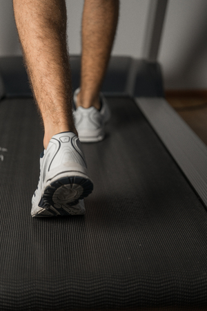 The legs of man running on treadmill in the gym. Health and sport concept. Healthy lifestyles