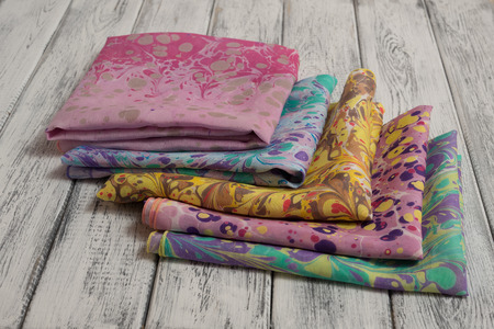 Châle pour femme en coton et soie, sur fond de bois clair. Concept Journée internationale de la femme Banque d'images