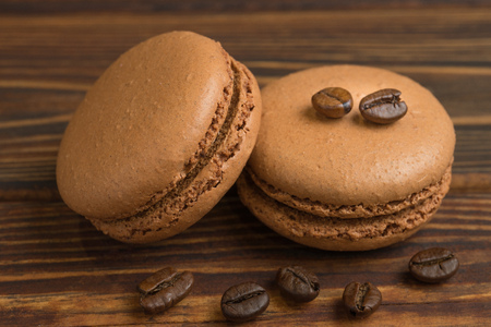 Chocolate macaroons with coffee beans, on the dark wooden table. Sweet macarons. Top view Stock Photo