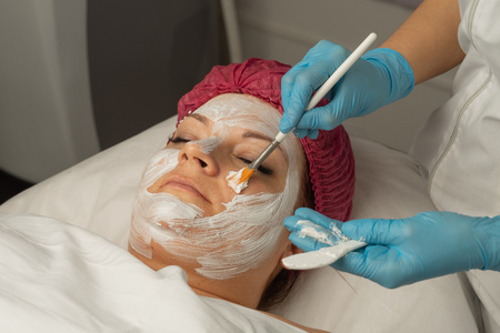 a cosmetologist makes a a pore-minimising mask on.