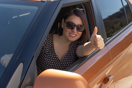 Woman is gesturing thumbs up sitting inside a new suv. 写真素材