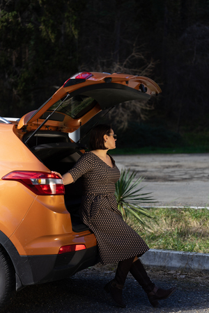 Woman relaxing inside car trunk and watching on forest