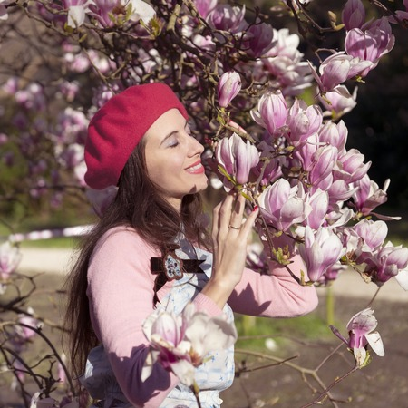 A woman sniffs the magnolia flower Stock Photo