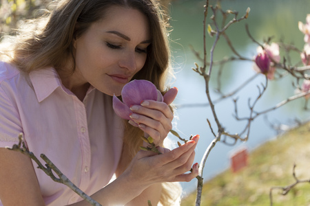 Woman is smelling magnolia bud in the spring garden by the lake