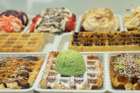 Traditional Belgian dessert - waffle with icecream and cream on the store shelves in Brussels 写真素材