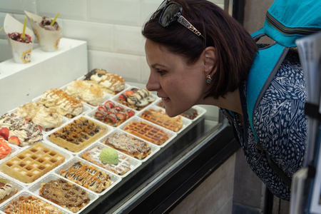 A girl is looking at popular street food, Belgium waffle and traditional dessert.