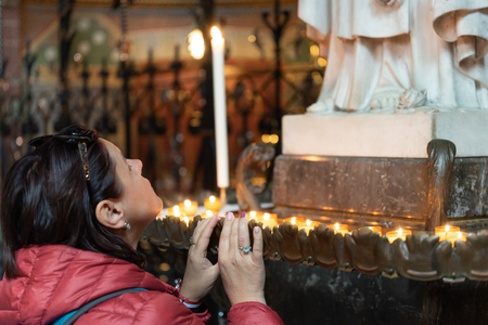 A young woman praying in a church Stock Photo