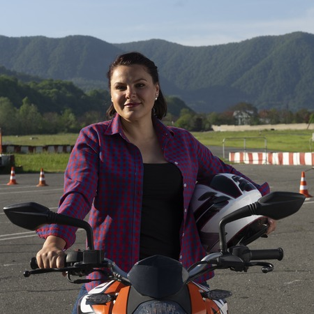 Girl on a scooter holding a helmet in a motorcycle driving lesson Imagens