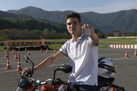 A young man graduated from the driving school, he shows driving licence for motorcycle