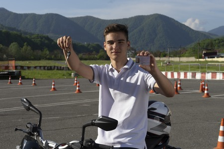 Young man on the motorbike is showing driving license and motorcycle keys. Motorcycle school Imagens