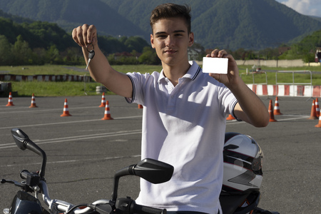Teen on the scooter is showing driving license and motorcycle keys. Copy space. Driving course Imagens