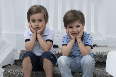 Childrens fashion. Beautiful twin brothers in elegant clothes are sitting close to each other