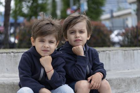 Portret van twee-eiige tweelingen op buiten in stijlvolle kleding. Kindermode en stijl