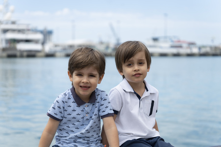 Two twin brothers of the model are sitting next to each other in fashionable clothes on the background of the sea.