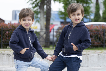 Cute four year old fraternal twins in fashionable clothes are posing for the camera