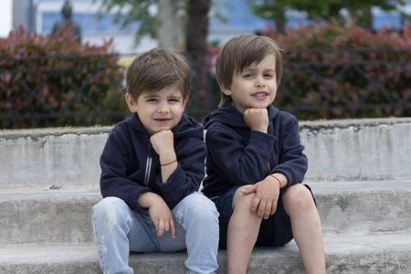 Two twin brothers are sitting next to each other in fashionable clothes. The concept of children's fashion and style