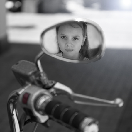 Reflection of girl child in rearview mirror motorcycle . The concept of child safety on the roads Black and white photo Stock fotó