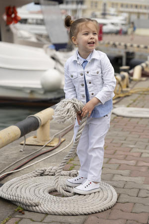 Kid girl is posing as fashion model. Child dressed in a fashionable denim suit. Childrens fashion 写真素材