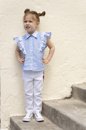 Fashion baby dressed in casual stylish clothes - white jeans, sneakers and blue blouse