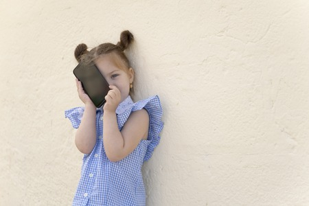 Little girl is playing with phone. Kid girl studying smartphone