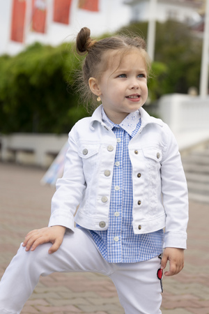 Kid model is dressed in a white denim suit. Child girl advertises fashionable childrens things participating in a photo shoot