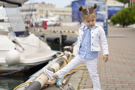 Little girl model on the marina dressed in stylish and fashionable clothes. The kid participates in a photo shoot to advertise childrens things